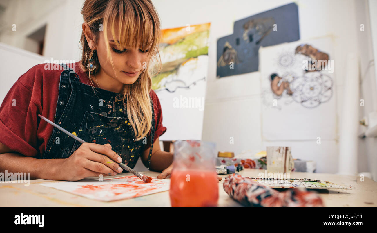 Shot of beautiful young female artist painting in studio. Woman painter drawing on paper in her workshop. - Stock Image