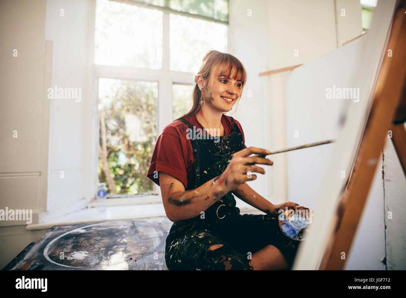 Indoor shot of female artist painting in studio. Woman painter painting in her workshop. - Stock Image
