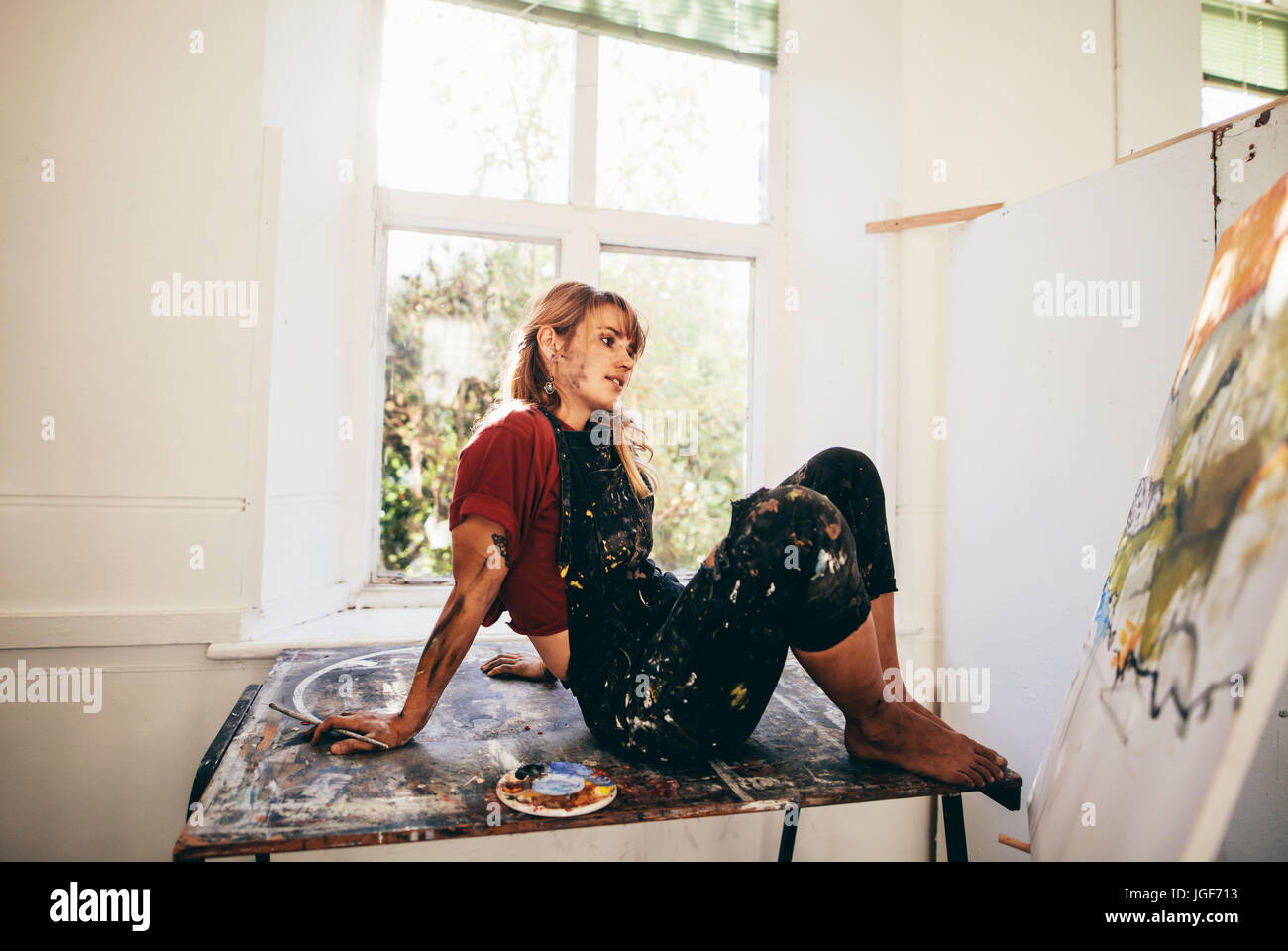 Indoor shot of female painter working in studio. Relaxed young woman artist looking at painting in her workshop - Stock Image