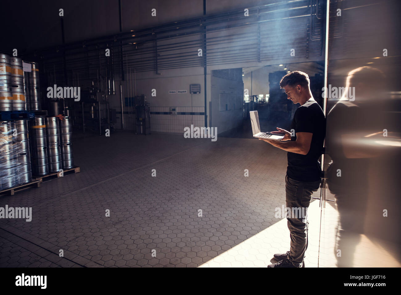 Horizontal shot of young man standing in brewery factory working on laptop. Brewery factory owner using laptop. - Stock Image