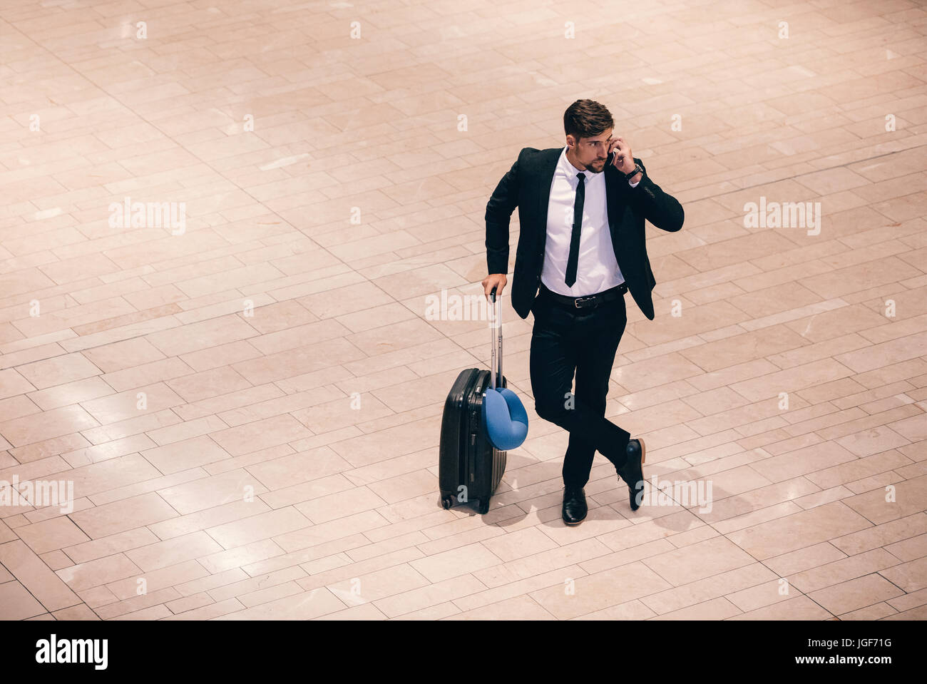 Top view shot of young businessman standing at airport terminal with suitcase and talking on phone. Business traveler - Stock Image