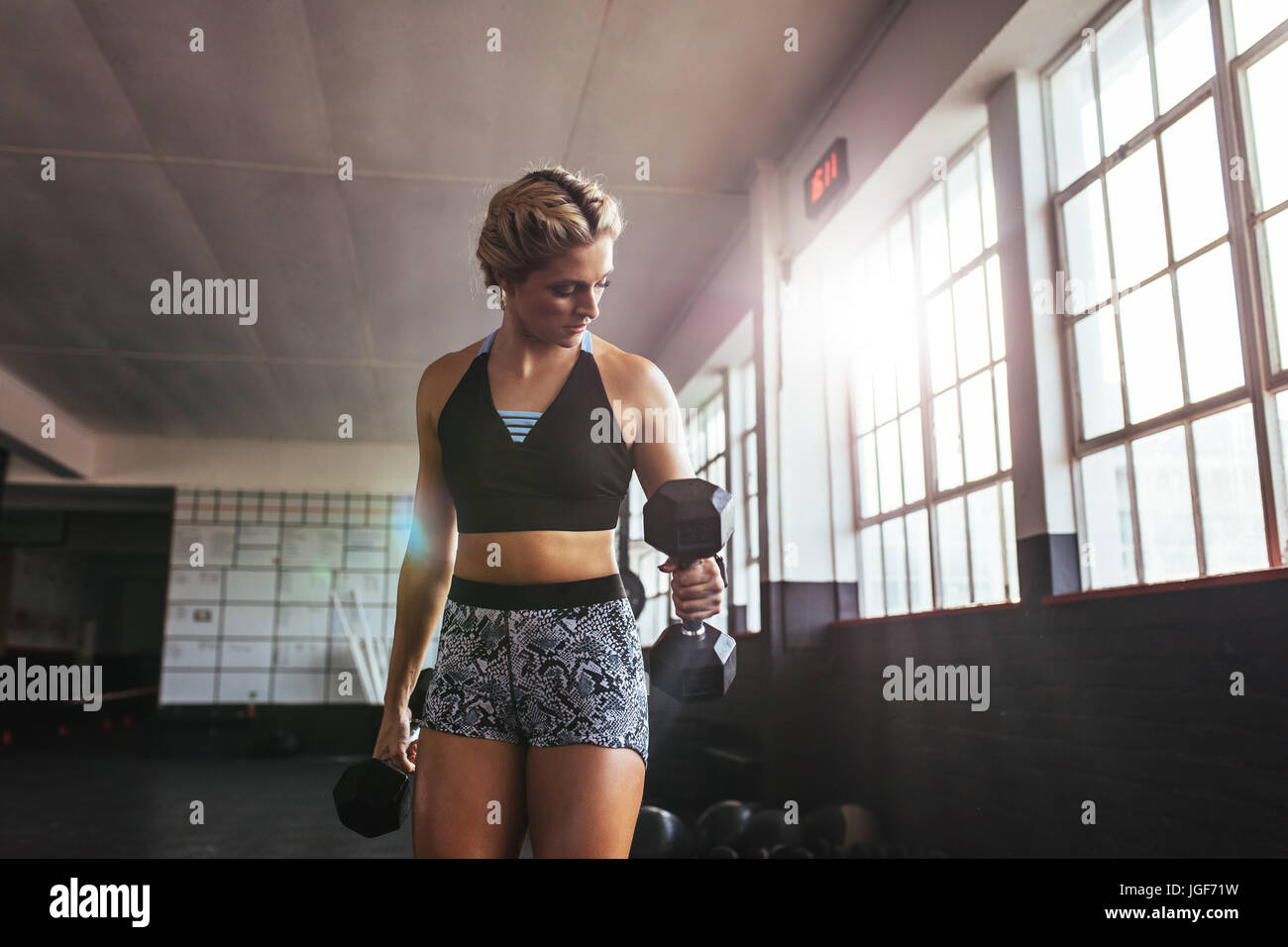Young woman pumping muscles using dumbbells. Athlete excercising with dumbbells for muscle and strength building. - Stock Image