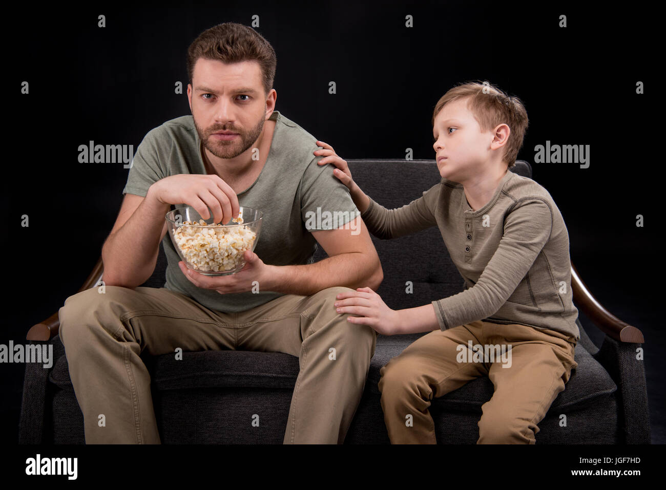 Little boy trying to talk with father eating popcorn and watching tv on sofa, family problems concept - Stock Image