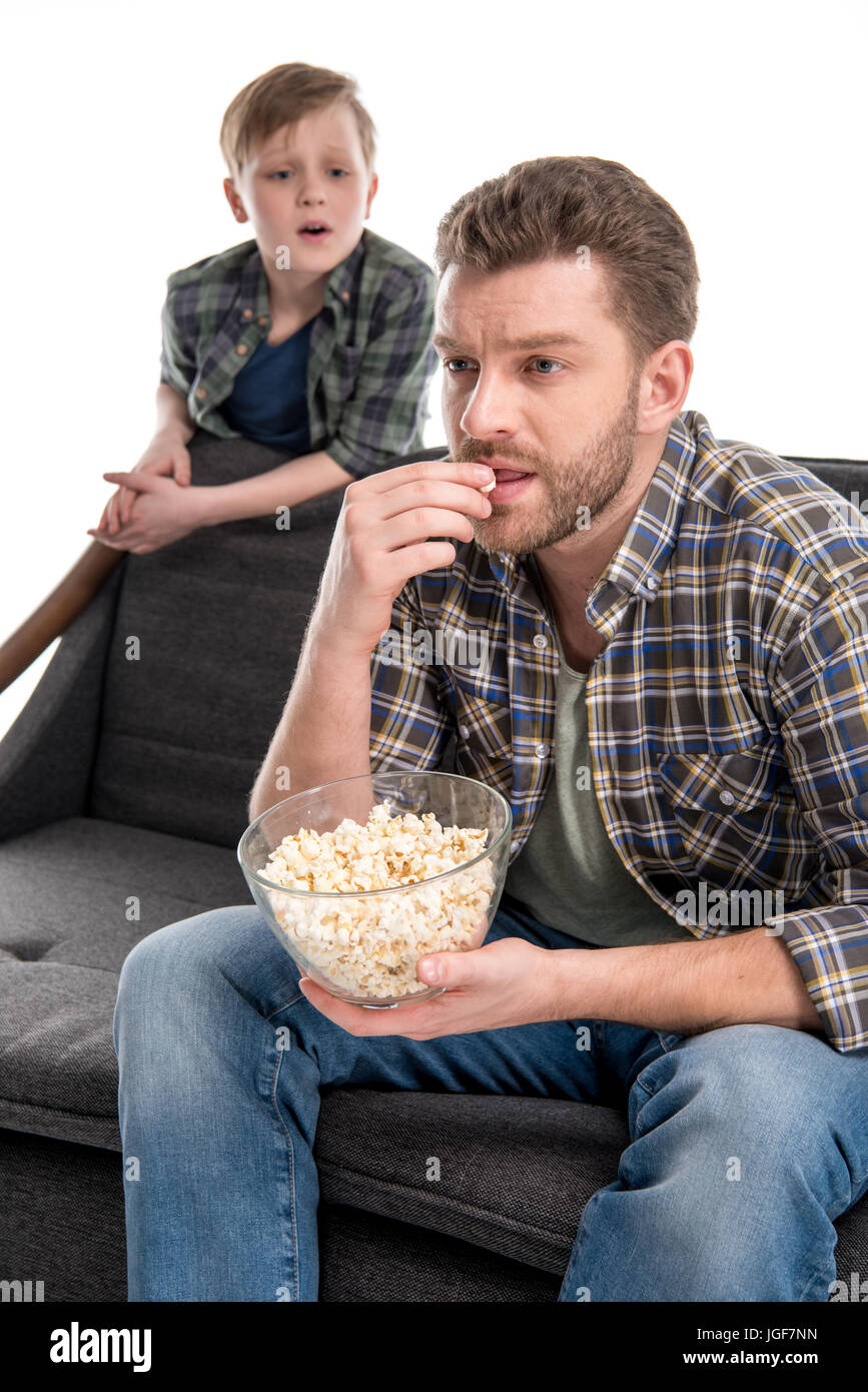 Son talking with father sitting on sofa and eating popcorn from bowl, family problems concept - Stock Image