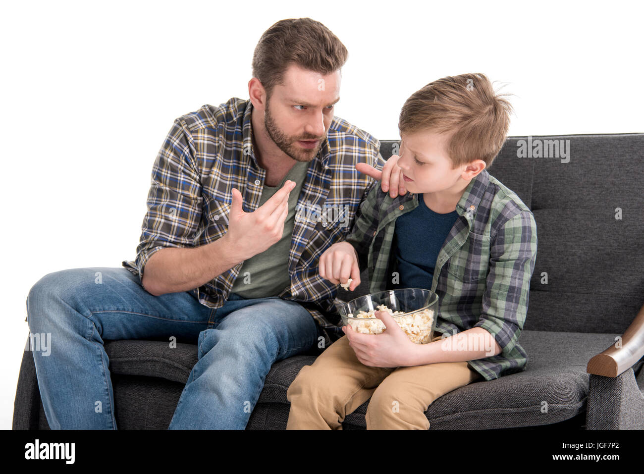 Father talking with son sitting on sofa and eating popcorn from bowl, family problems concept - Stock Image