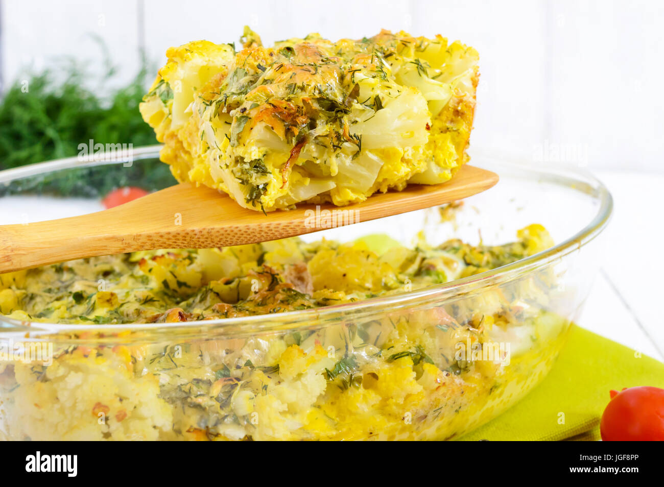 Baked cauliflower with cheese and egg in a glass form on a white wooden background. A large piece of casserole on - Stock Image