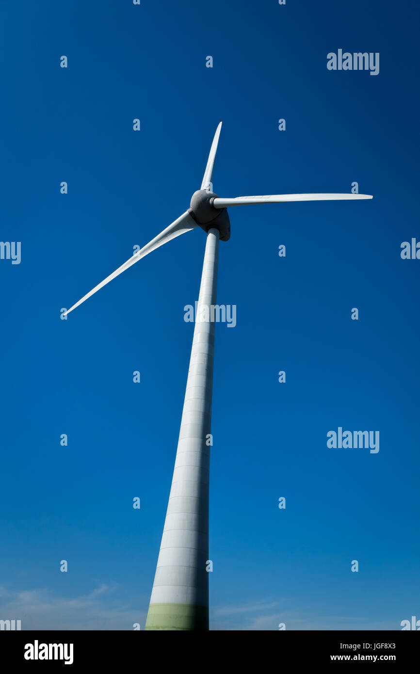 wind energy turbine / modern wind mill against blue sky background - Stock Image