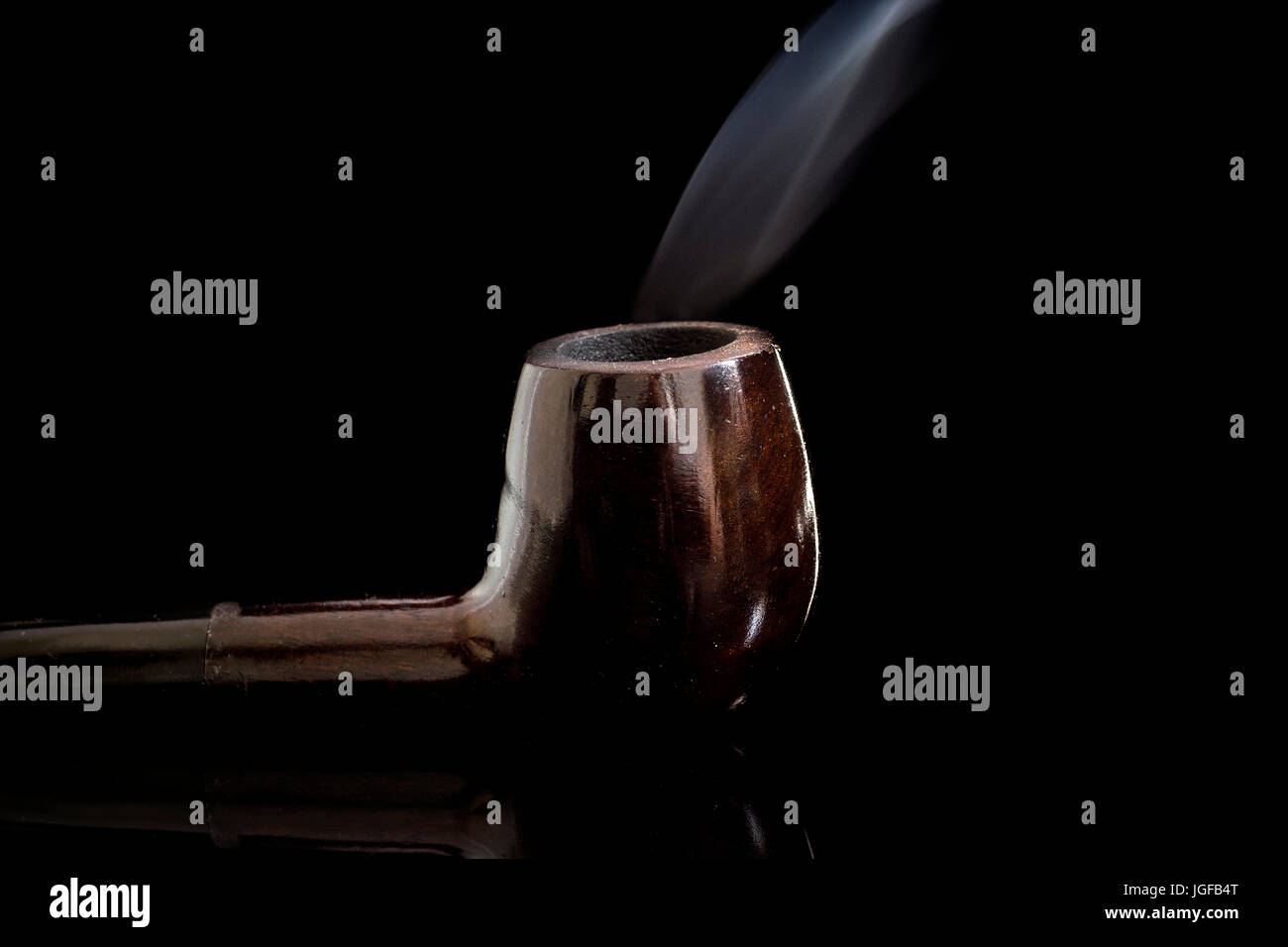 Lit Tobacco Smoking pipe reflective glass surface, with moving smoke, low key black background - Stock Image