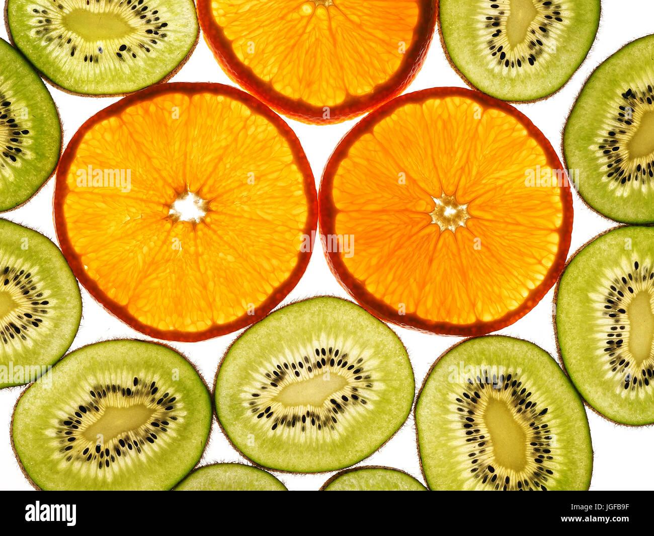 Kiwi with orange slices on the white background - Stock Image