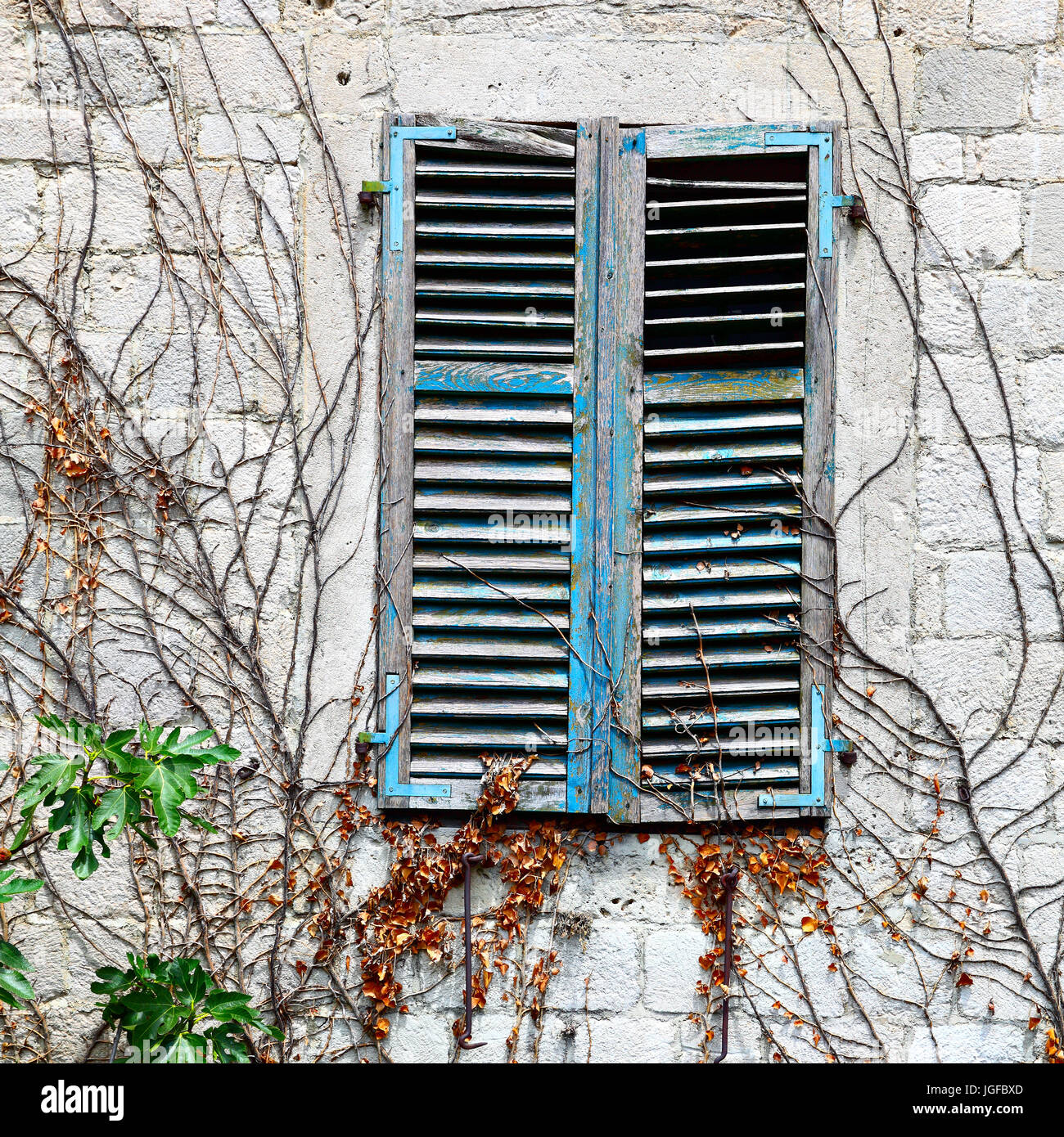 Old houses Old house window with closed shutters - Stock Image