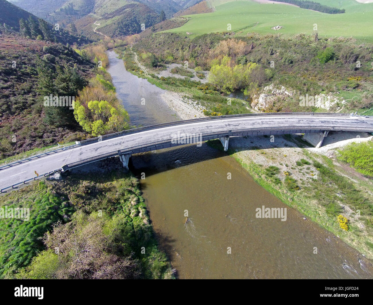 Curved bridge over Opuha River, between Geraldine and Fairlie, South Canterbury, South Island, New Zealand - drone aerial Stock Photo