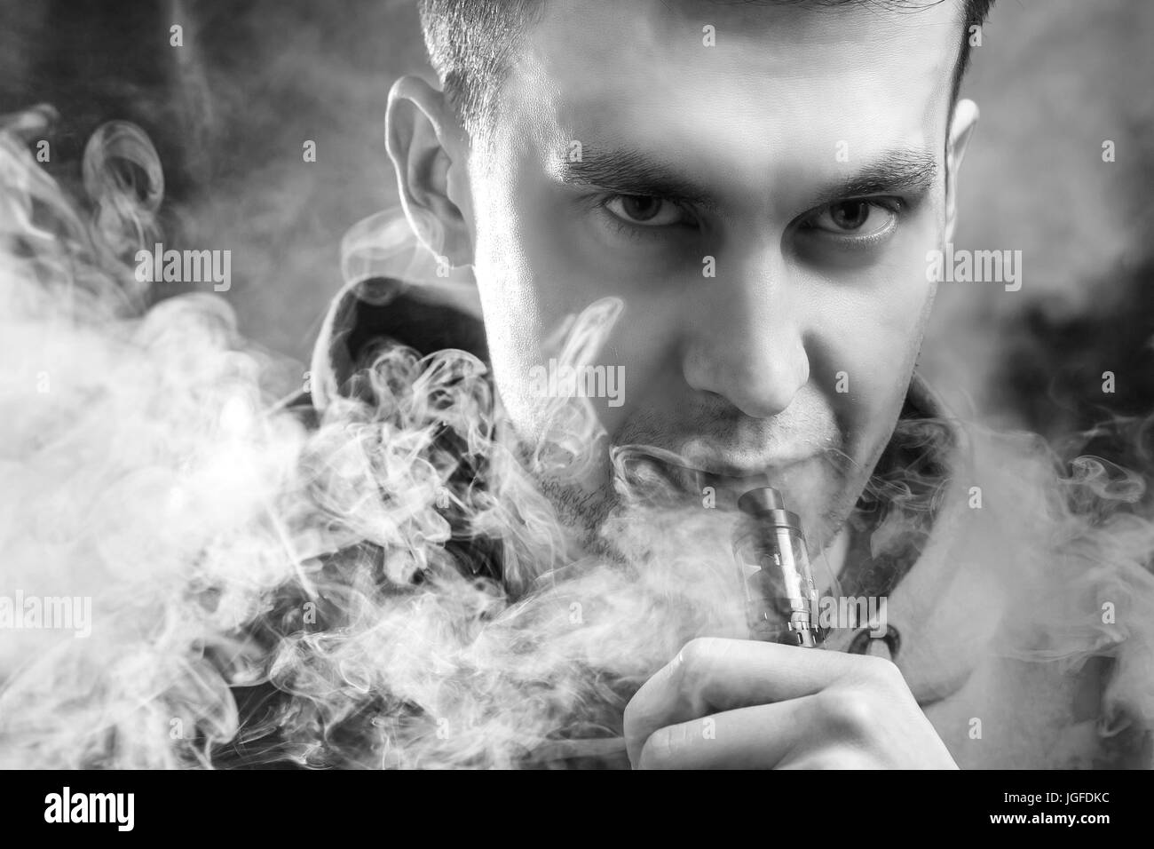 A man smokes a vape, lets steam, studio, colored smoke. Black and White - Stock Image