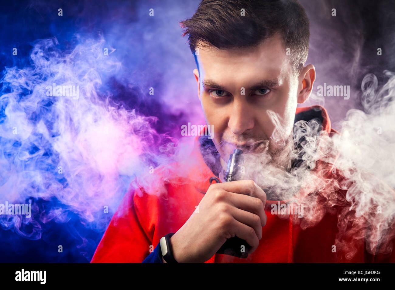 A man smokes a vape, lets steam, studio, colored smoke. - Stock Image