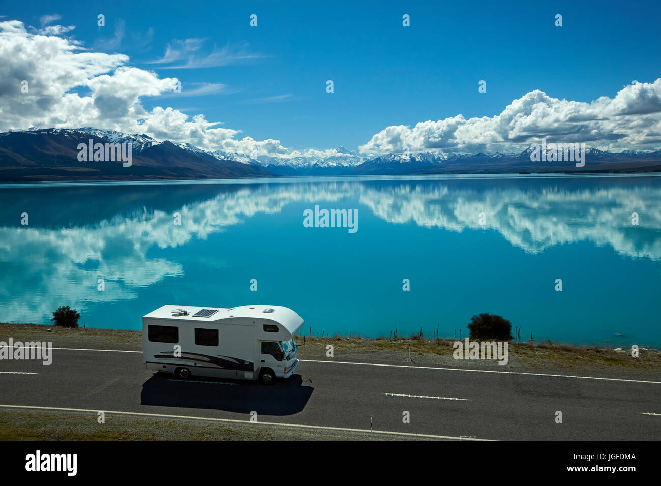 Campervan on State Highway 8, and Aoraki / Mount Cook reflected in Lake Pukaki, Mackenzie Country, Canterbury, South - Stock Image