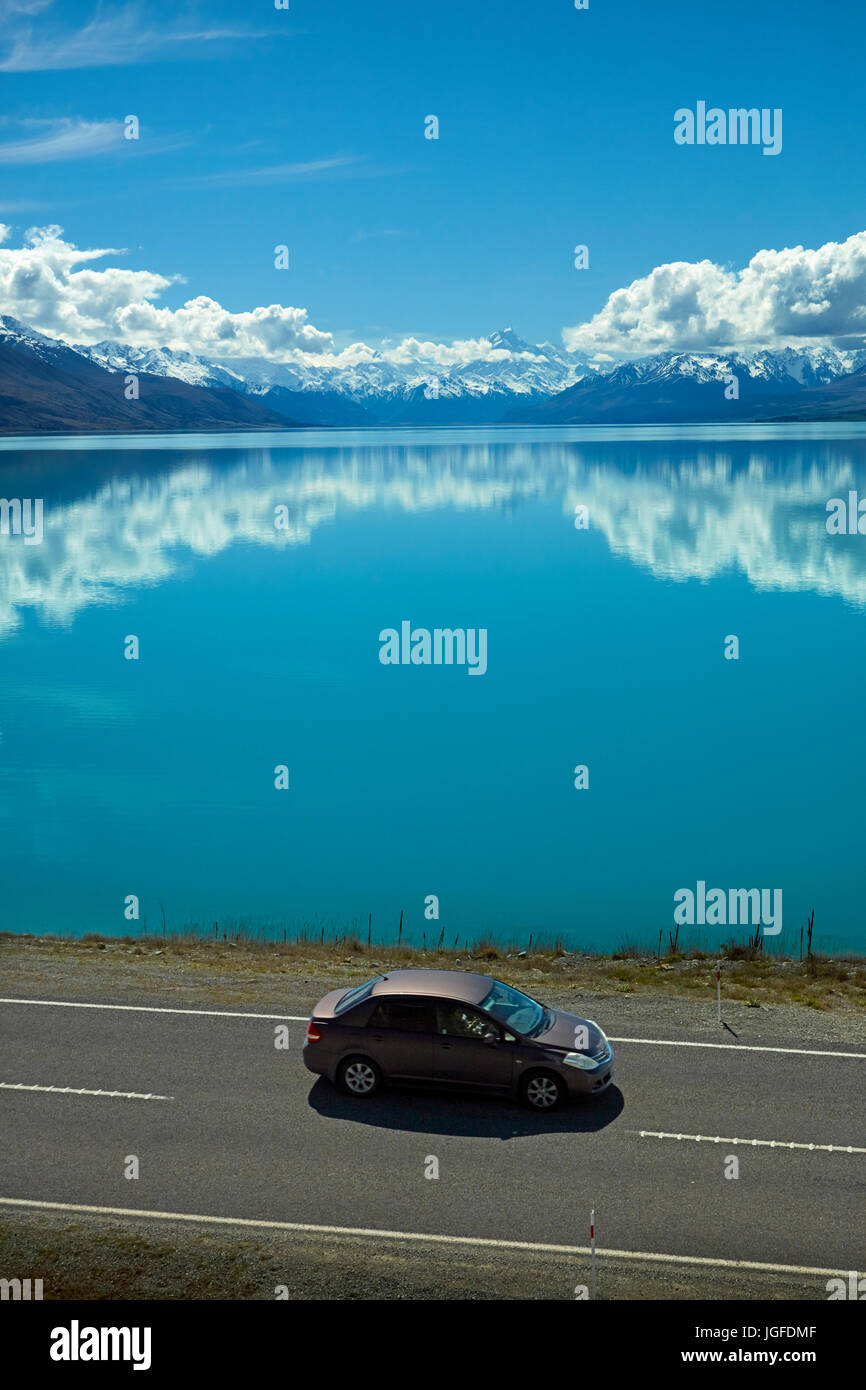 Car on State Highway 8, and Aoraki / Mount Cook reflected in Lake Pukaki, Mackenzie Country, Canterbury, South Island, - Stock Image