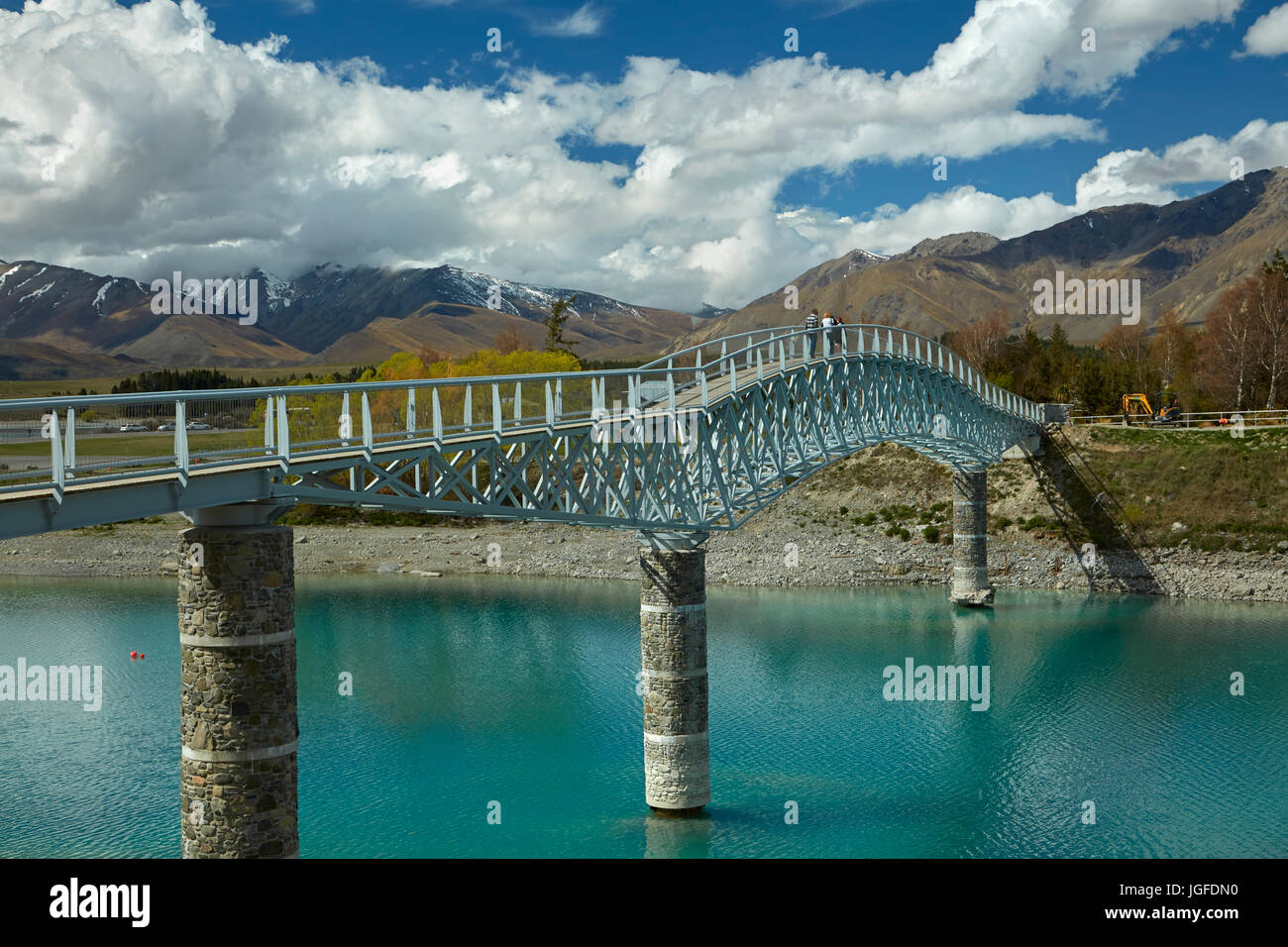 Tourists on pedestrian Bridge over Lake Tekapo outlet to Church of the Good Shepherd,  Mackenzie Country, Canterbury, - Stock Image