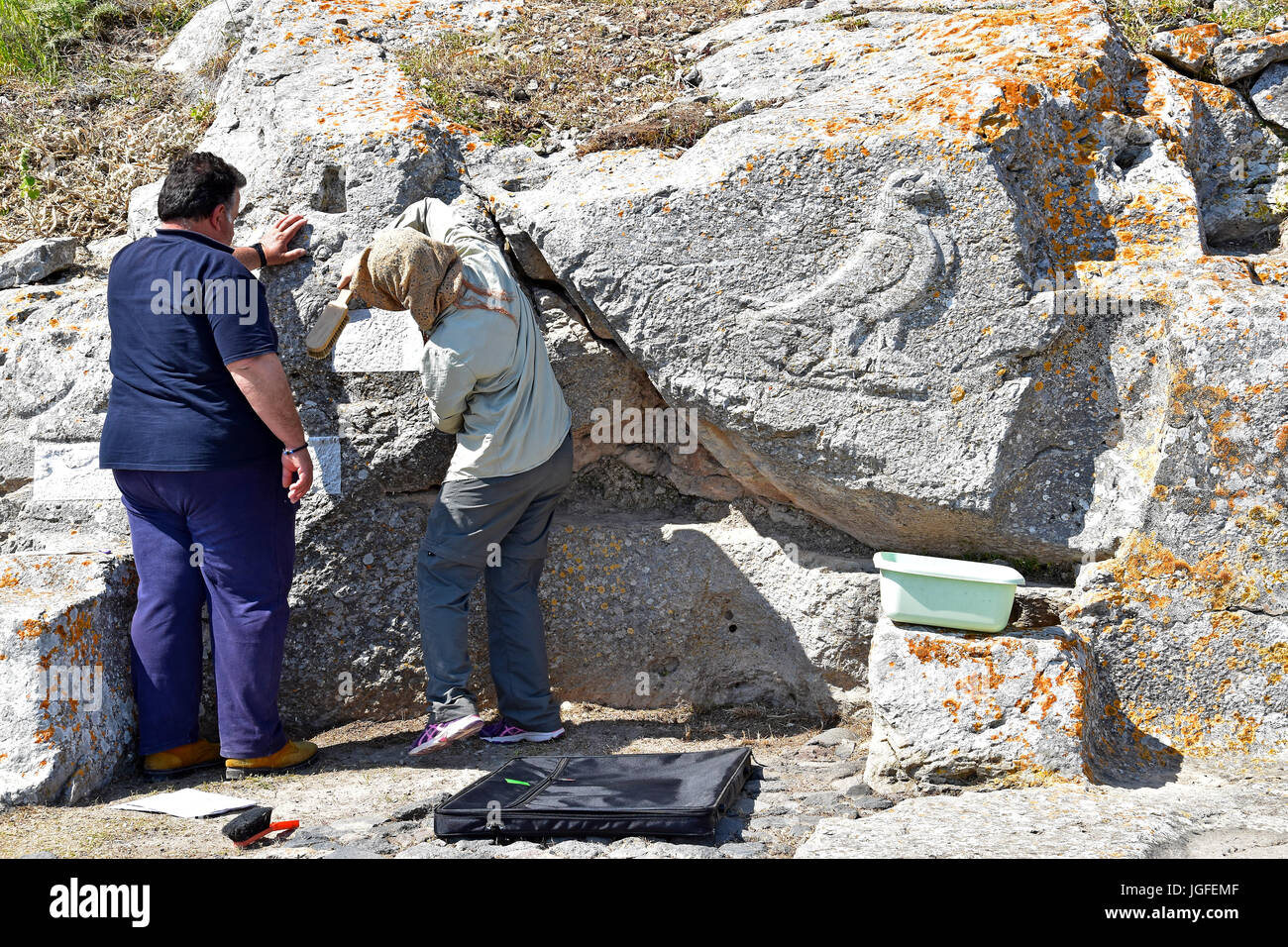 Greeks restoring carvings on the remains of Ancient Thira, Sanctuary of Artemidoros Kamari, Santorini, Greece - Stock Image