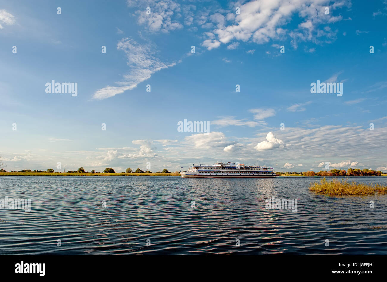 Beautiful summer view of the ship at the bend of the river bed at sunset in the summer. The horizontal frame. Stock Photo