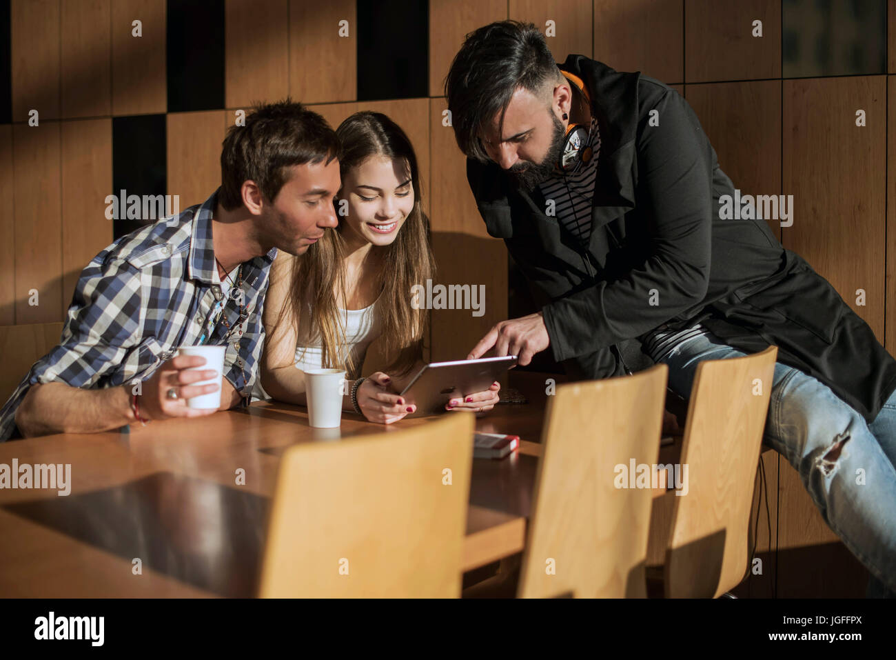 Group of friends sitting in the room by the table and comunicate. - Stock Image
