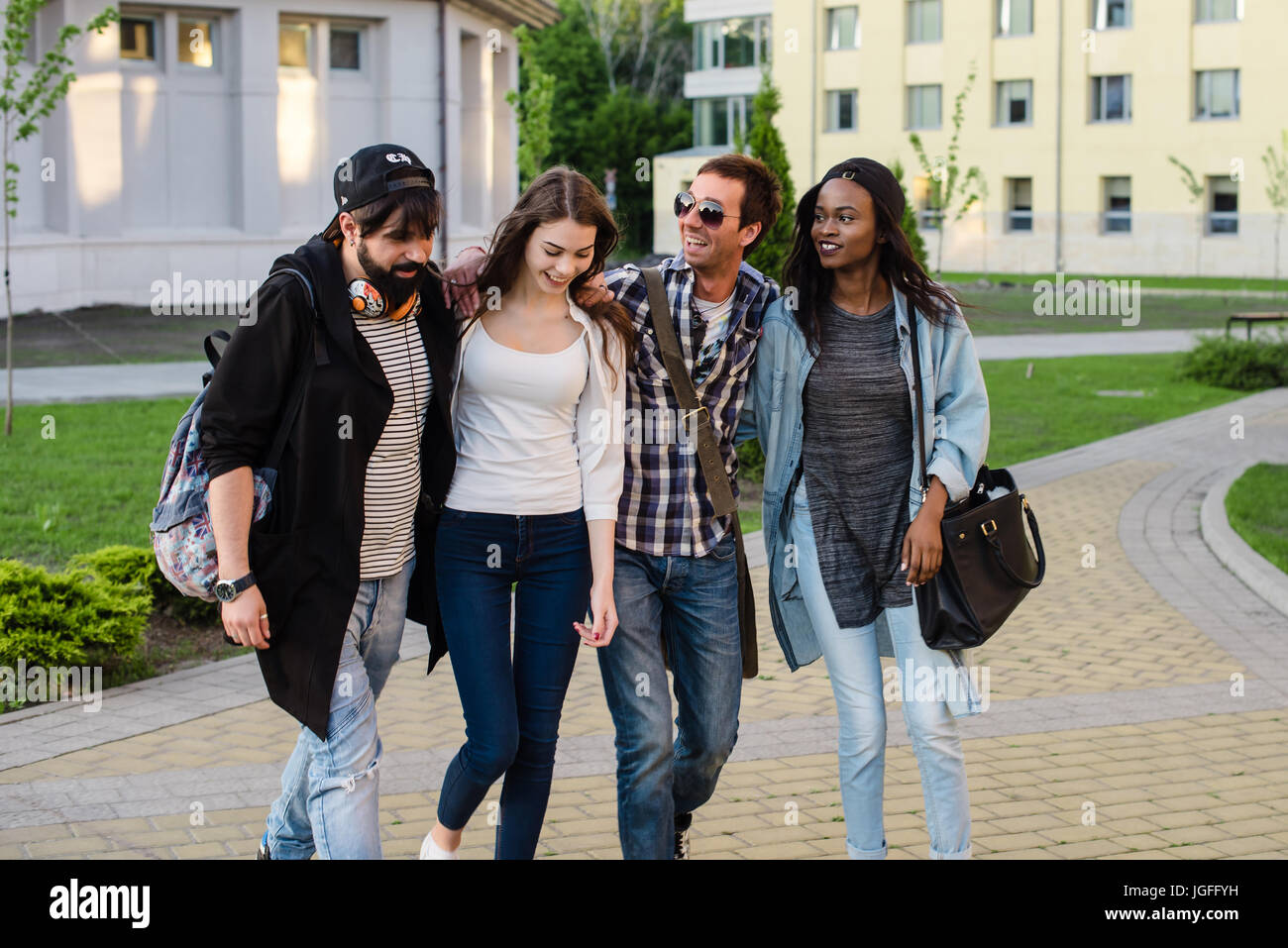 Four happy friends walking on campus and talking. Two boys and rwo girls wearing casual clothes. - Stock Image