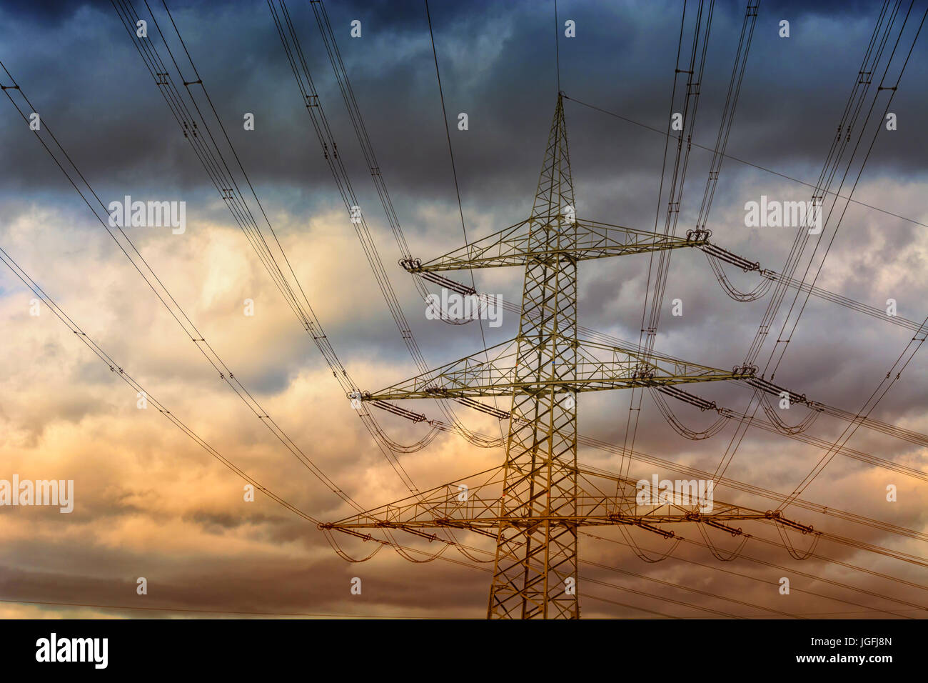 Electricity mast or also high voltage line in the background a cloudy sky. - Stock Image