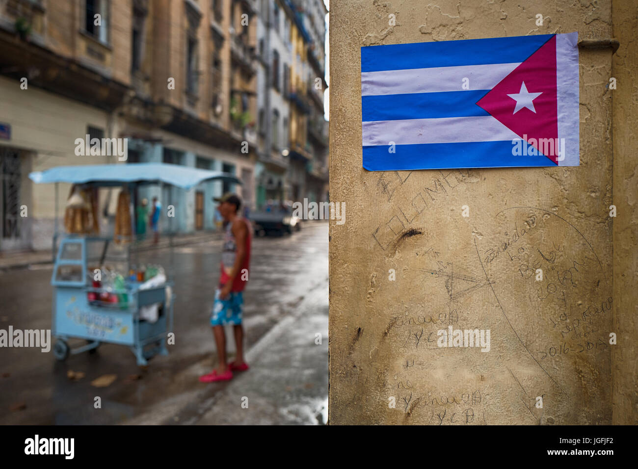 differentially focused image of a sreet food seller and focused Cuban flag on a graffiti marked wall. Havana, Cuba. - Stock Image
