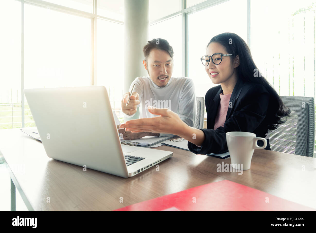 Couple of young designers working at modern office, two coworkers discussing fun project over a laptop, little team - Stock Image