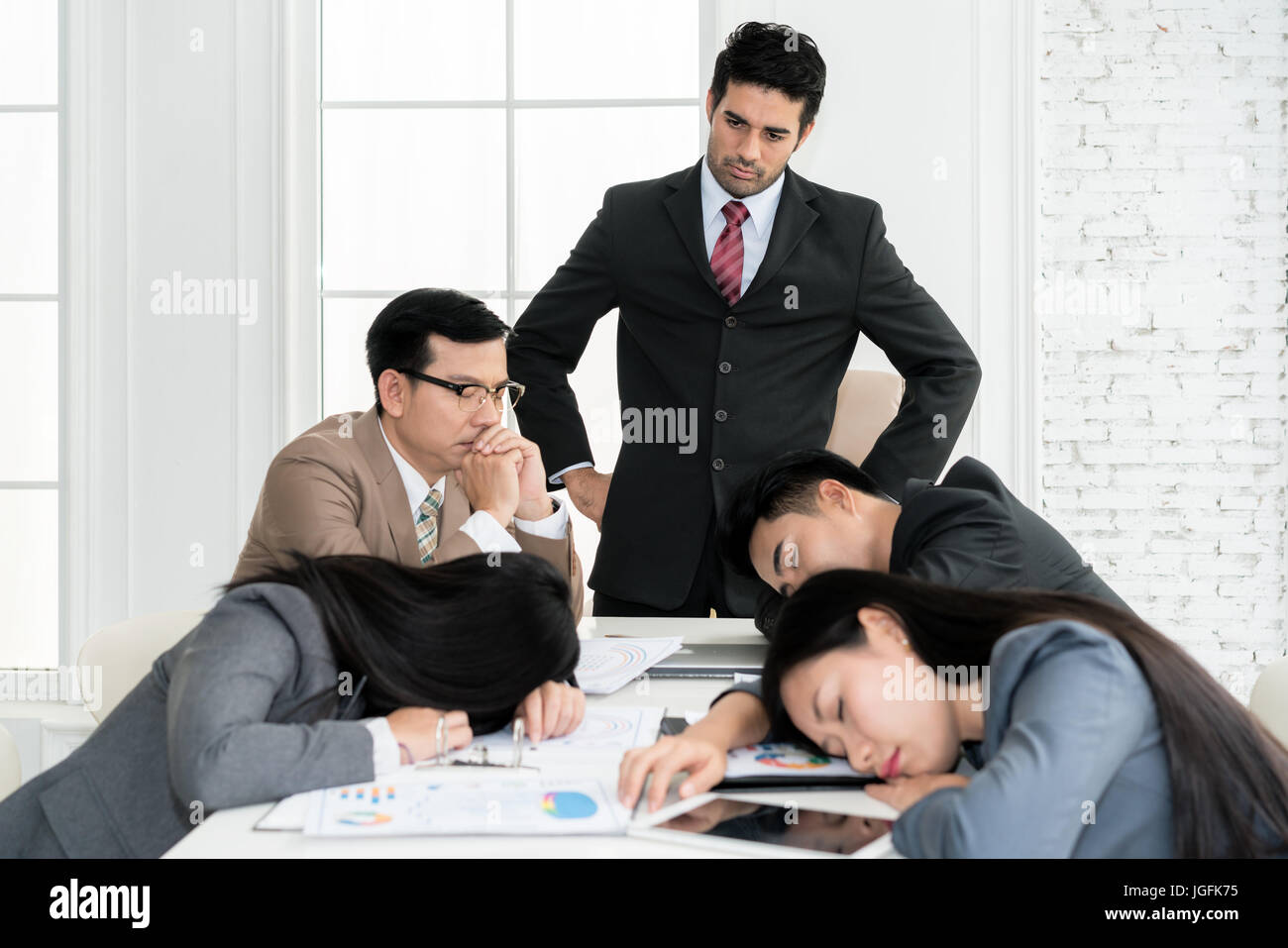 Boss angry when business people team sleeping on meeting room in office. Business people team tired after working - Stock Image