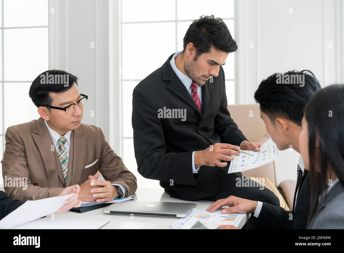 Asian smart manager explaining internal meeting to his project team in modern office. The multi ethnic business - Stock Image