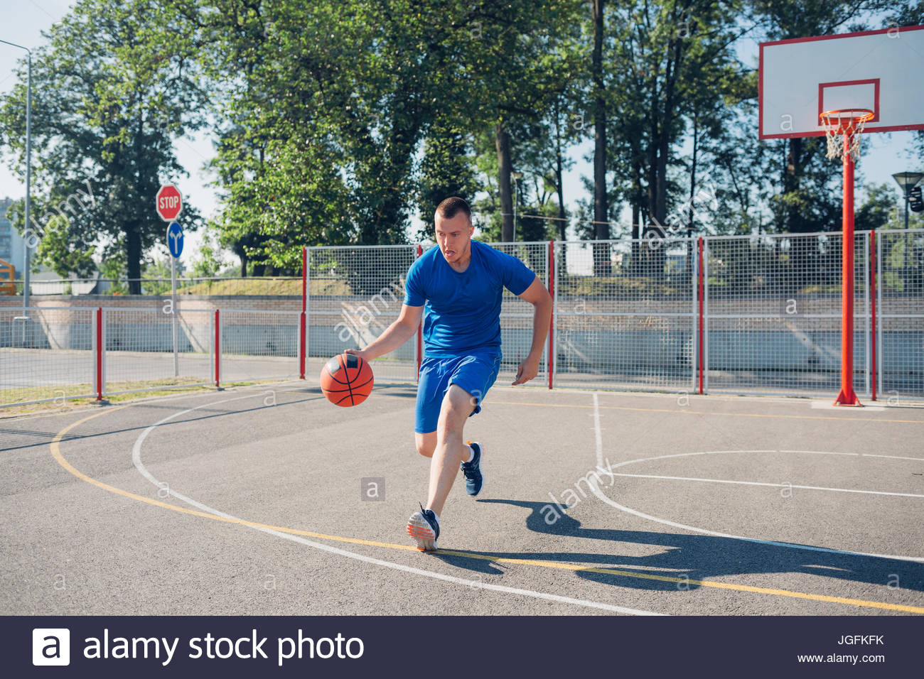 Young Caucasian basketball player dribbling a ball - Stock Image