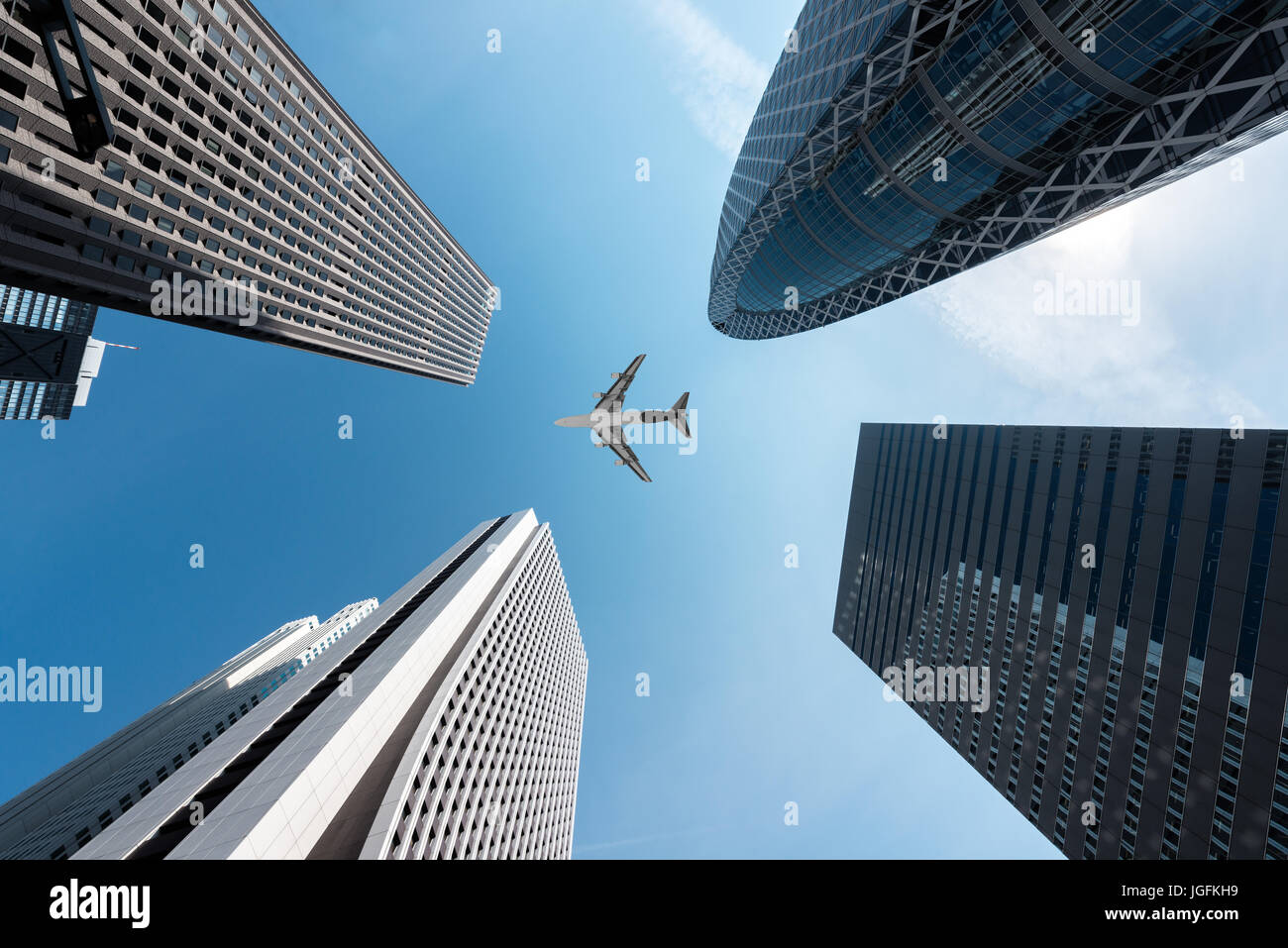 Tokyo skyscrapers buildings and a plane flying overhead at in Tokyo Shinjuku downtown and business district in morning - Stock Image