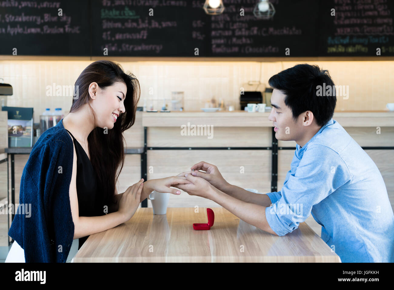Asian handsome man putting wedding ring on and proposing to his beautiful woman in cafe. Love, anniversary, surprise, - Stock Image