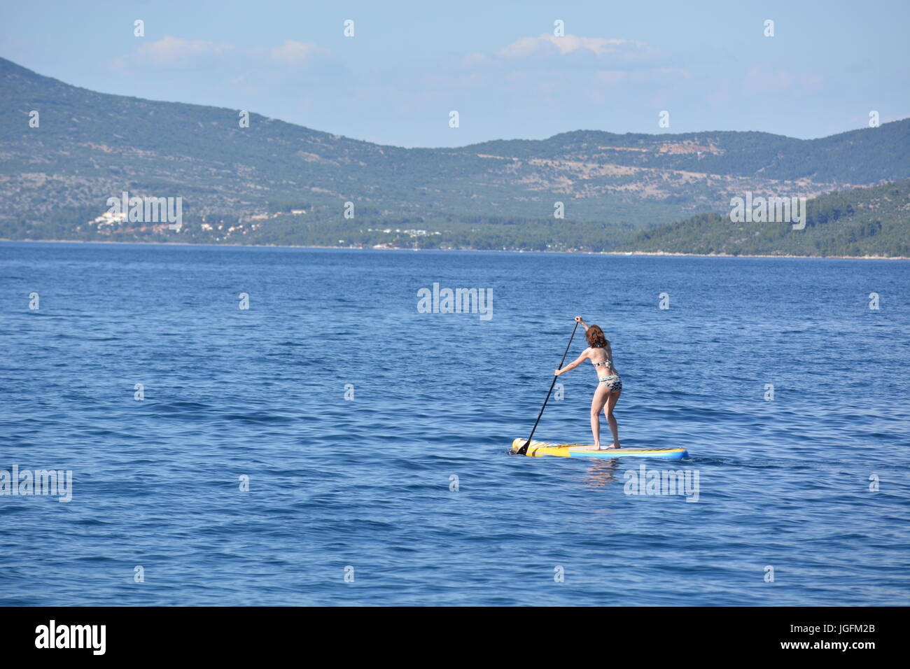 Cres, Croatia - June 18, 2017 - Girl on stand up paddleboard Stock Photo