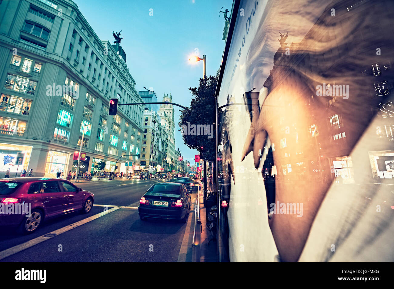 Reflection on a window shop poster in Gran Via Avenue. Madrid. Spain - Stock Image