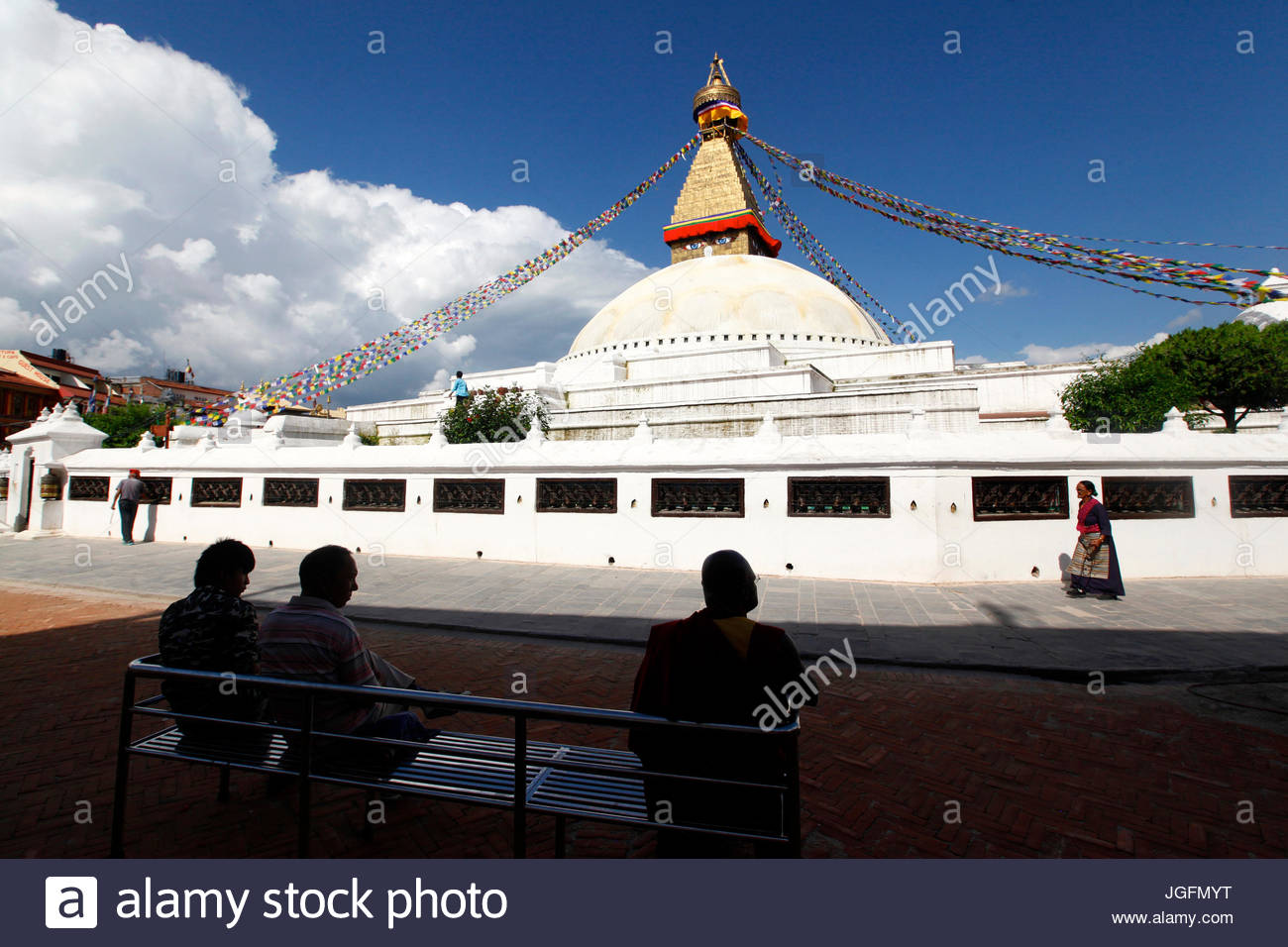 People sit on a bench admiring Boudhanath Stupa, the largest stupa in Nepal. - Stock Image