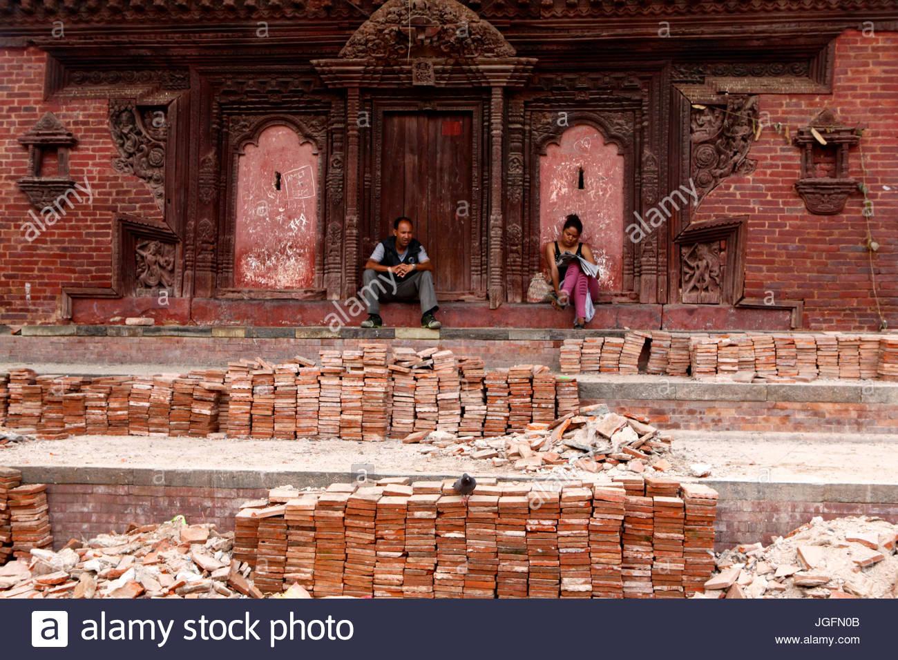 People sit amongst the bricks in Kathmandu's Durbar Square. - Stock Image