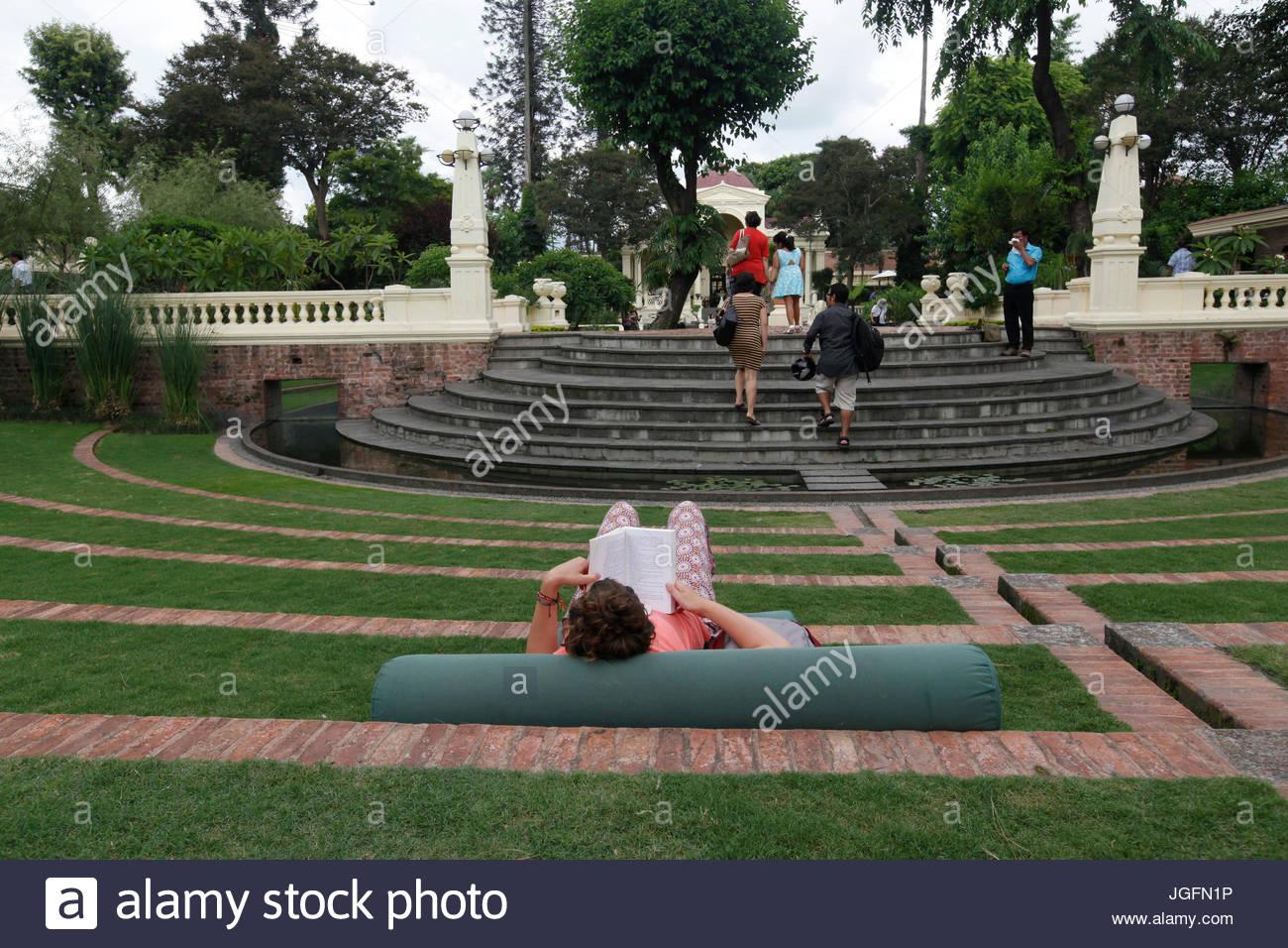 A woman reads inside Kathmandu's Garden of Dreams. - Stock Image
