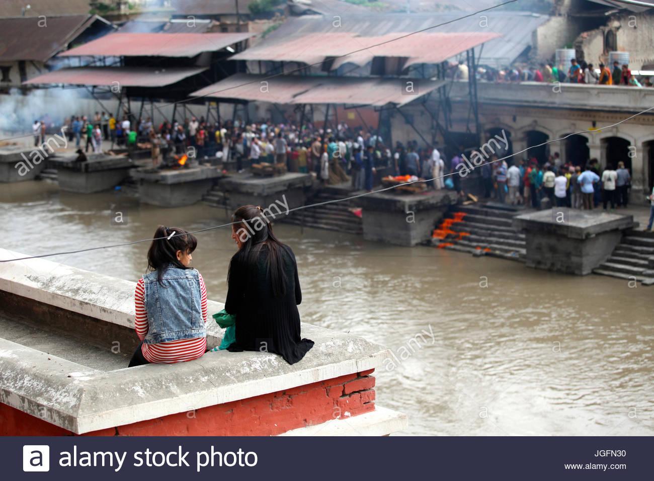 Girls watch Hindu cremations at Pashupatinath Temple. - Stock Image