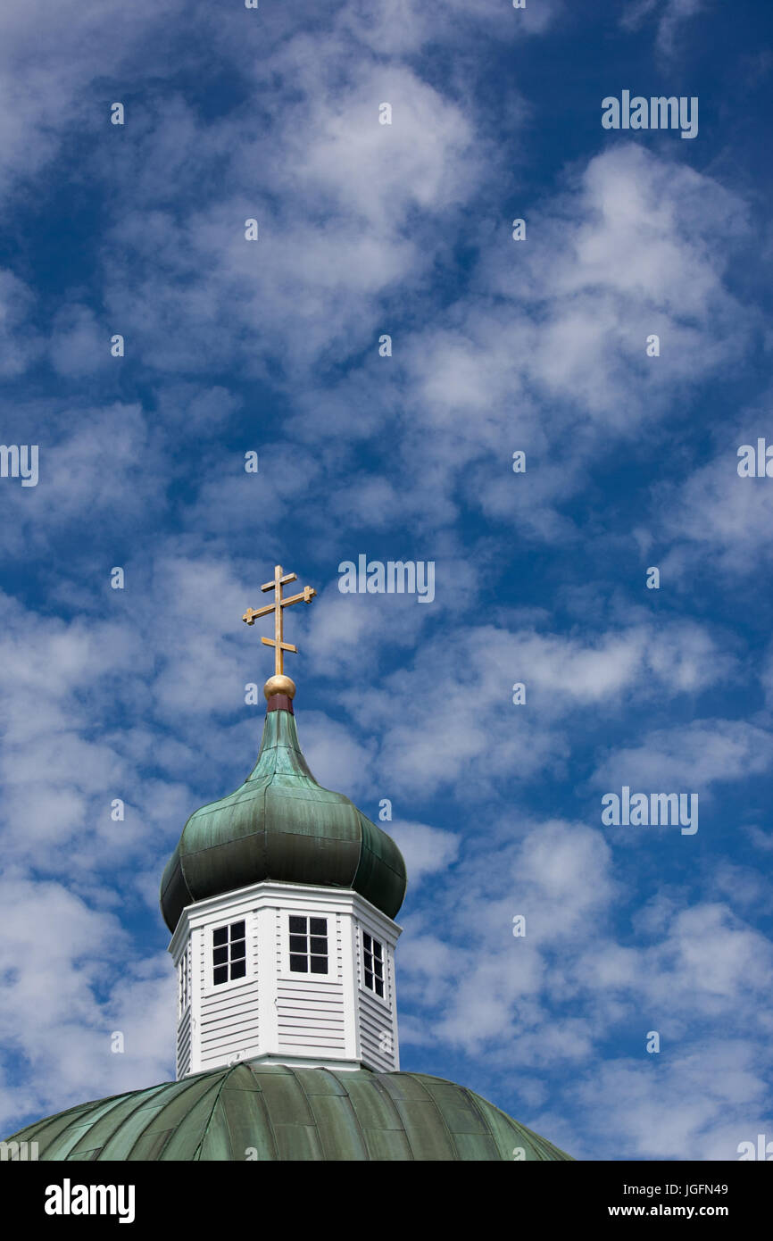 The cross at the top of Sitka's Saint Michael's Russian Orthodox Cathedral is visible against a cloudy sky. - Stock Image