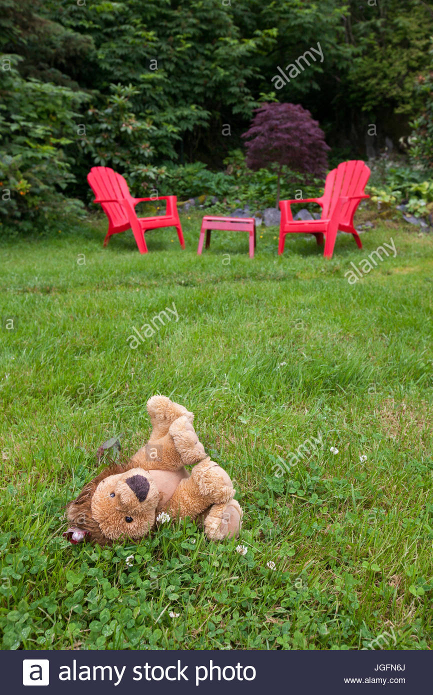 A stuffed animal lion lays in the grass near red lawn and patio furniture. - Stock Image