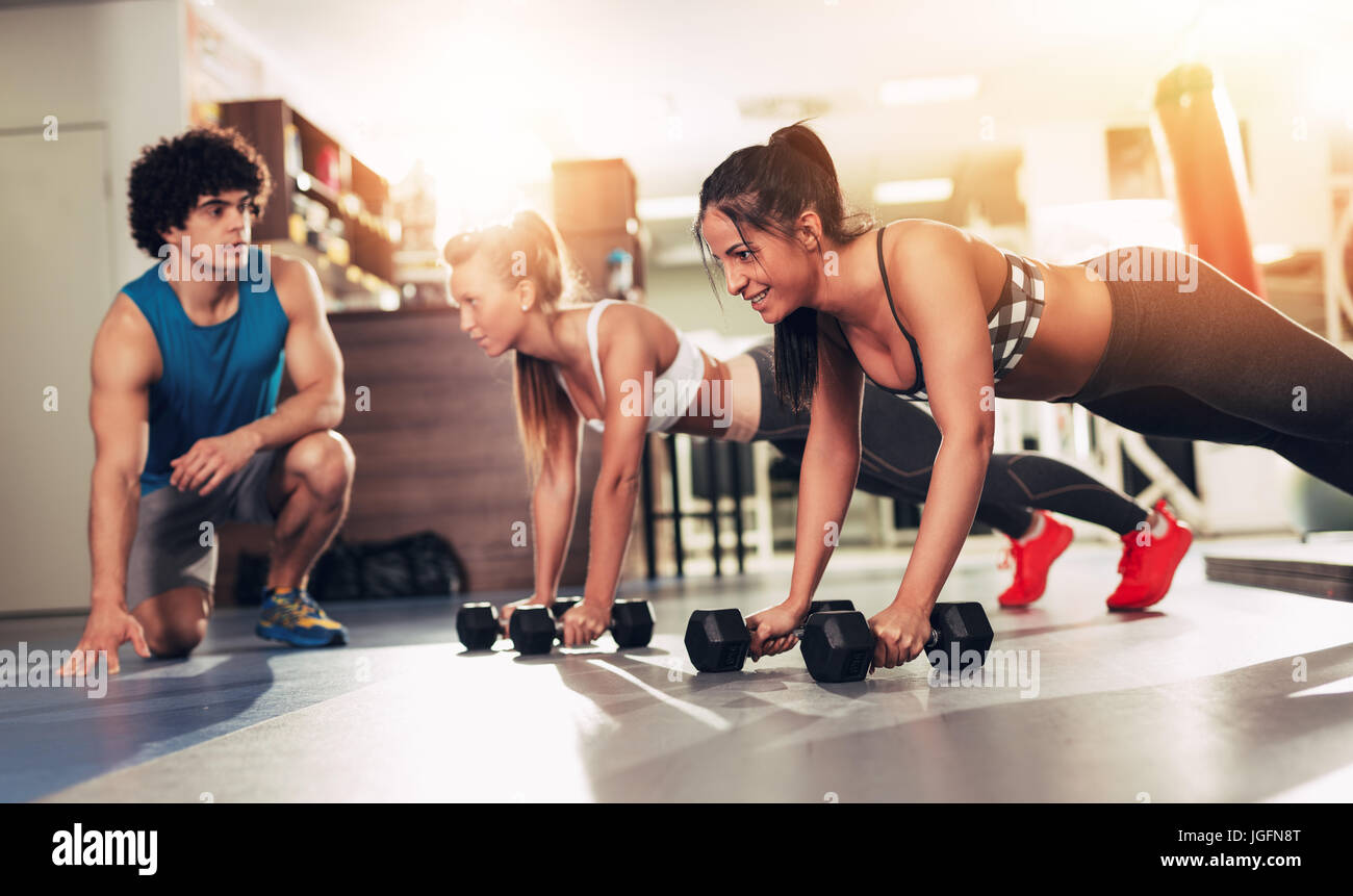 Two smiling girl exercising at the gym with a personal trainer. - Stock Image