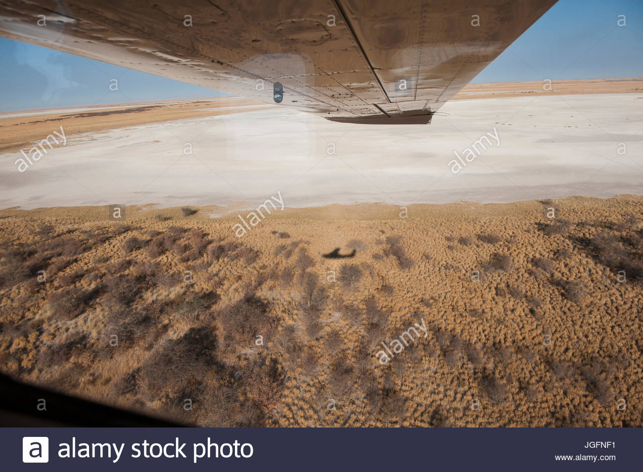 Vast and otherworldly, the salt pans of Botswana's Kalahari Desert dwarf a bush plane's shadow. - Stock Image