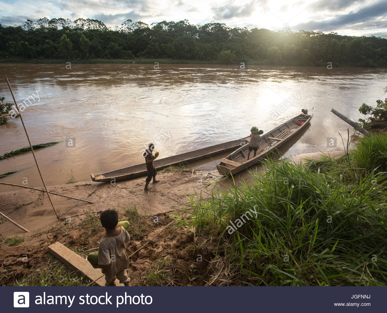 Tsimane people approach a canoe to transport goods on the Maniqui River, near Anachere, in the Amazon rainforest, - Stock Image