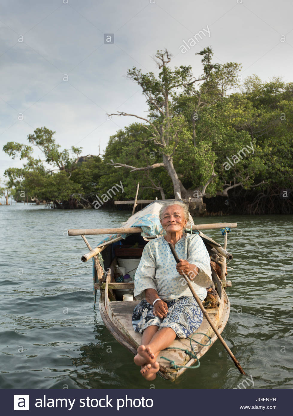 An old Bajau woman living all year round on a Lepa, a traditional houseboat. - Stock Image