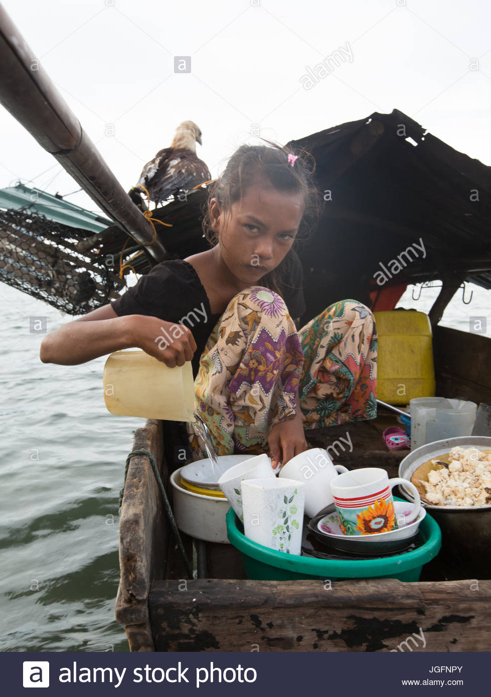 A Bajau girl, who lives all year round on a Lepa, a traditional houseboat. - Stock Image