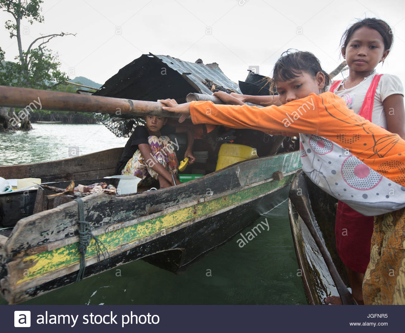 A Bajau family, who lives all year round on a Lepa, a traditional houseboat. - Stock Image