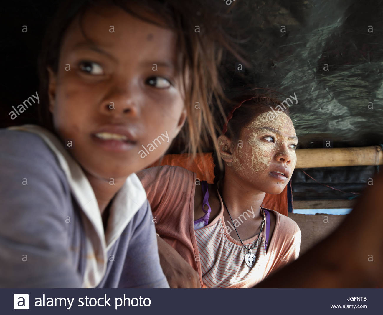 Her face dusted in bedak sejuk, a cooling powder made of rice and pandan leaves, a Bajau girl and her friend sit - Stock Image