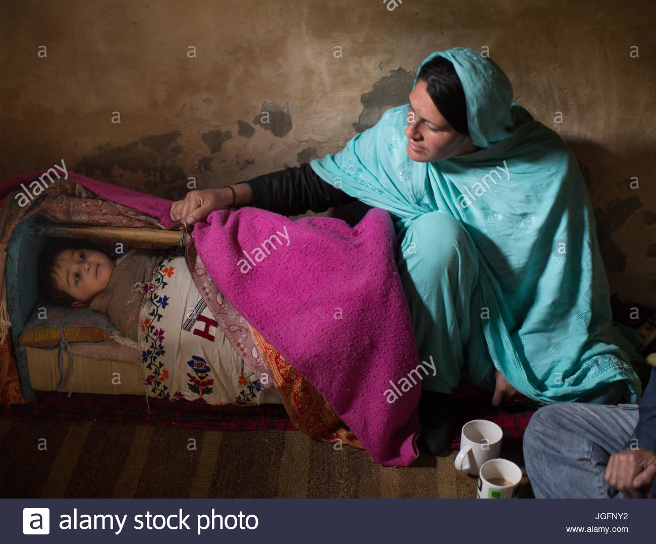 A woman watches over her baby at home in the Hunza Region. - Stock Image
