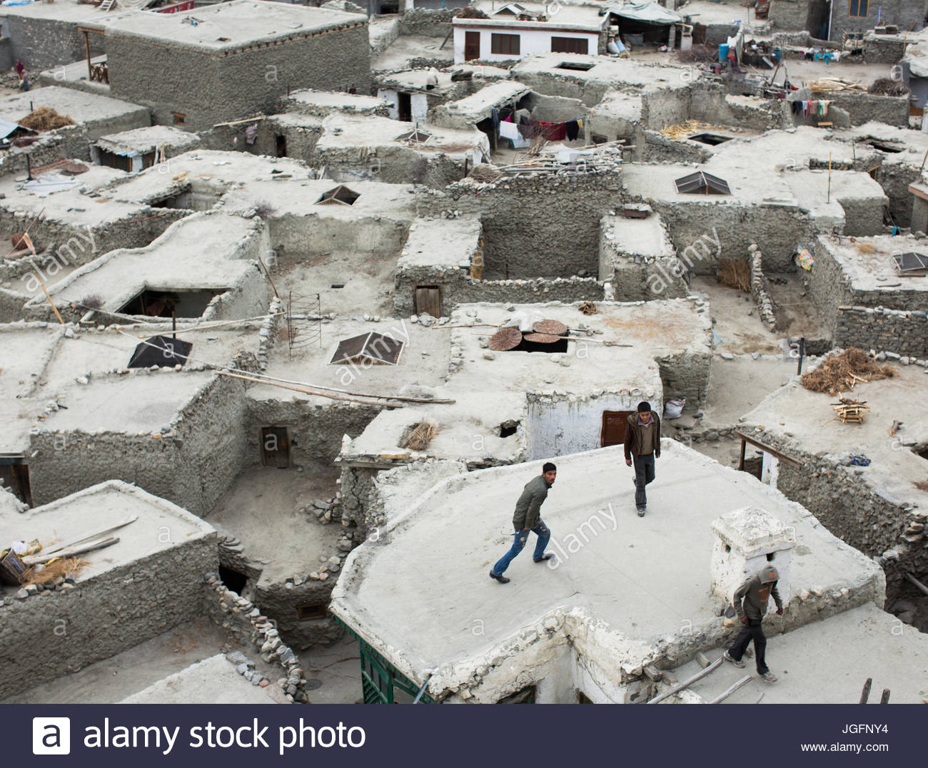 Teenager play on the roofs of houses in the village of Altit in the Hunza region. - Stock Image