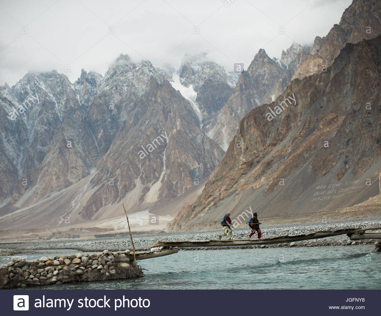 Crossing a river bed in the Hunza Valley, en route to getting wood for cooking and heating in Khuramabad. - Stock Image